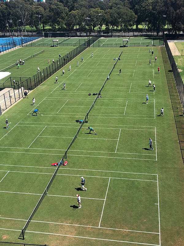 People playing tennis on natural turf tennis courts at the Memorial drive Centre