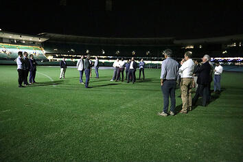 Group of people standing together on the Sydney Cricket Ground turf listening to SPORTENG team