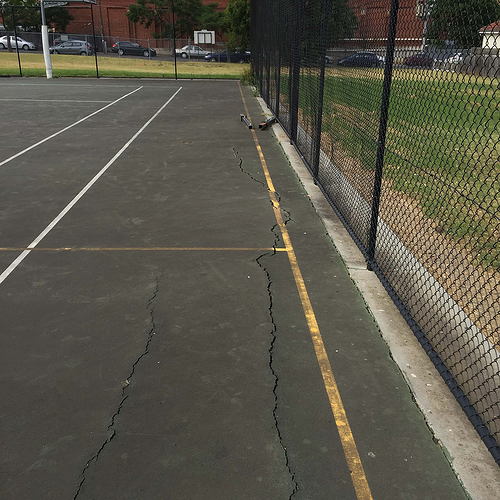 cracks in the middle of a netball Field of Play in the city